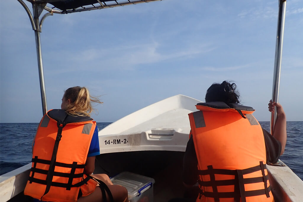 two people on boat in life jackets on whale watching tour in Trincomalee on east coast of Sri Lanka with Divinguru